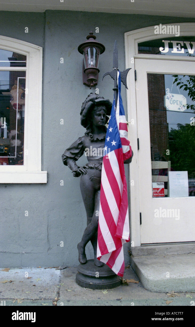 Antique statue with American flag in front of  antiquarian store New Hope Bucks County Pennsylvania USA - Stock Image