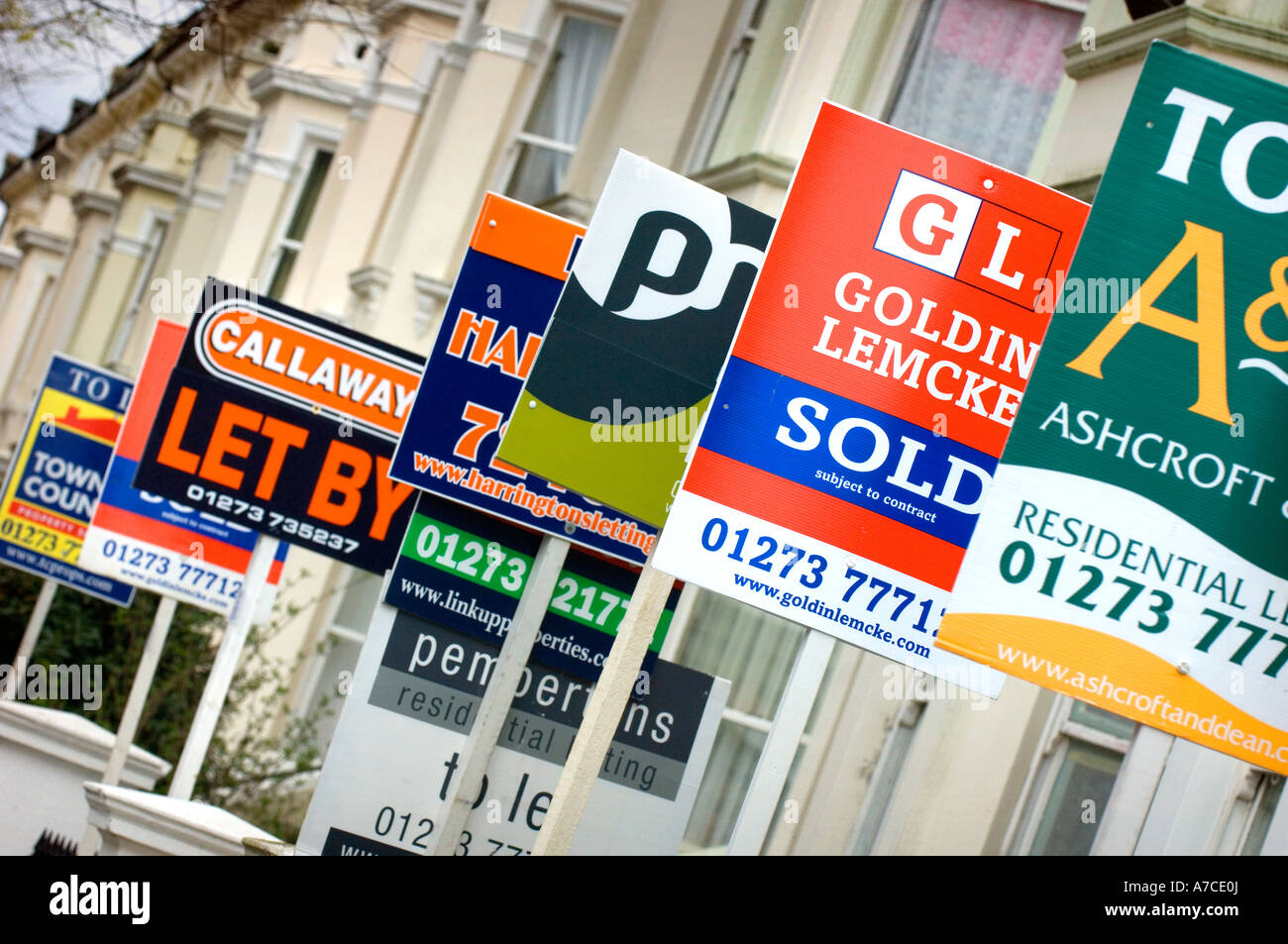 Estate agent for sale boards stacked up down a street. Picture by Jim Holden. Stock Photo