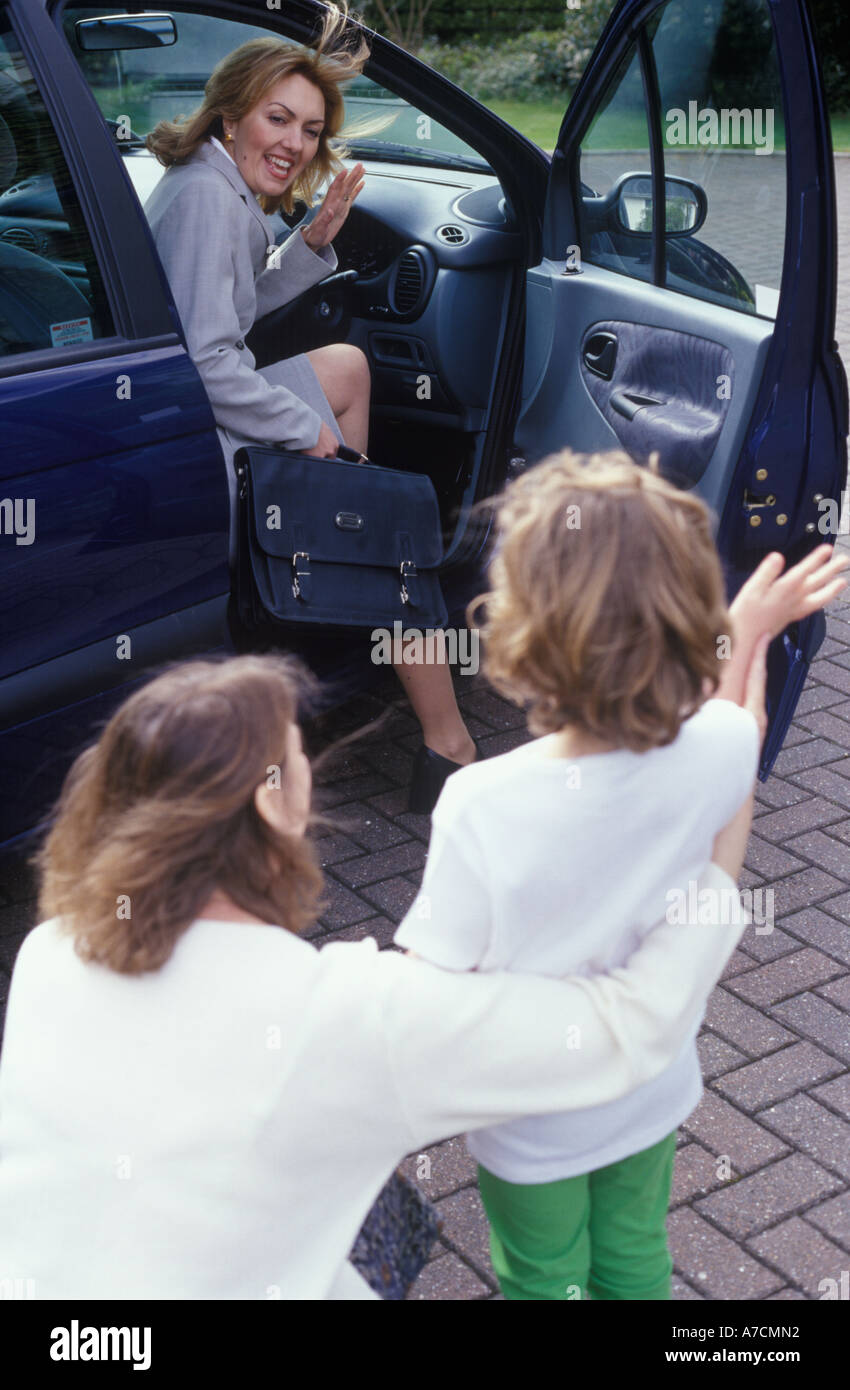 Mother waving goodbye to child as she gets into car - Stock Image