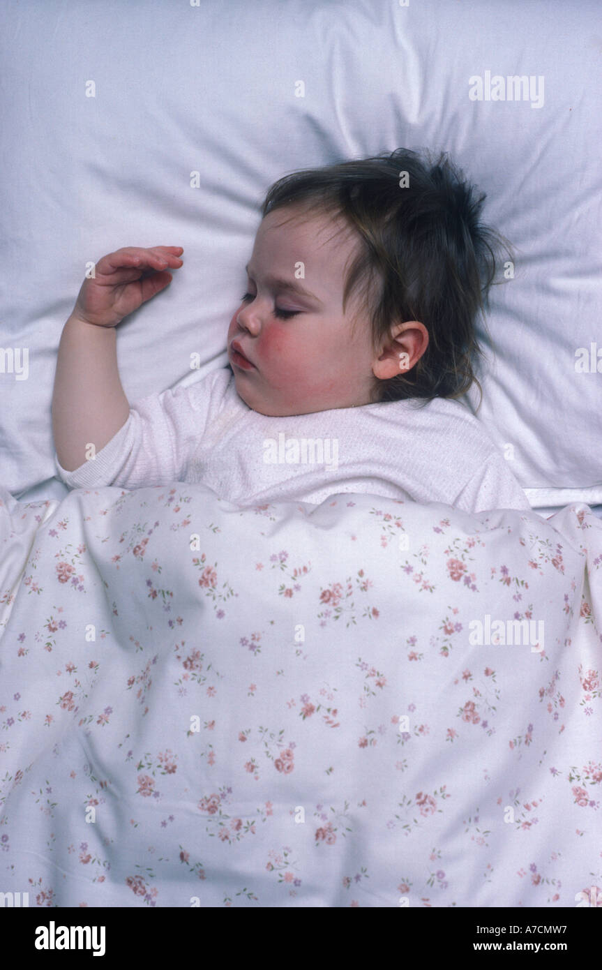 toddler ill with red cheeks asleep - Stock Image