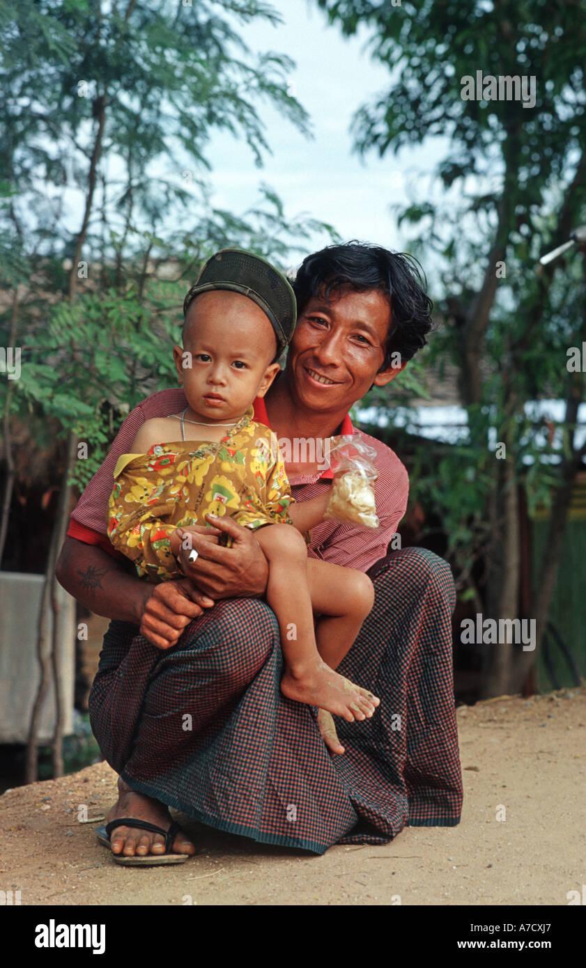 Friendly father carrrying child at Taungboyone Nat festival near Mandalay Burma - Stock Image