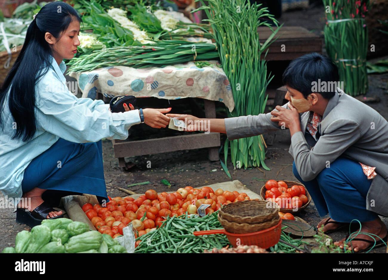 A market transaction Money changes hands Fruit vegetable vendor with face powder maiing a sale Market Pyin U Lwin Maymyo BURMA - Stock Image
