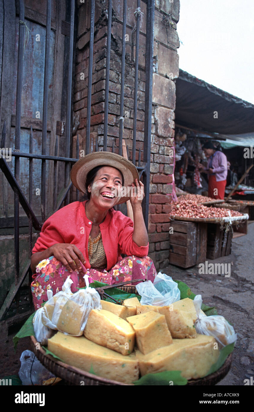 Laughing cheese vendor with face powder hat Market Pyin U Lwin Maymyo Central Burma - Stock Image