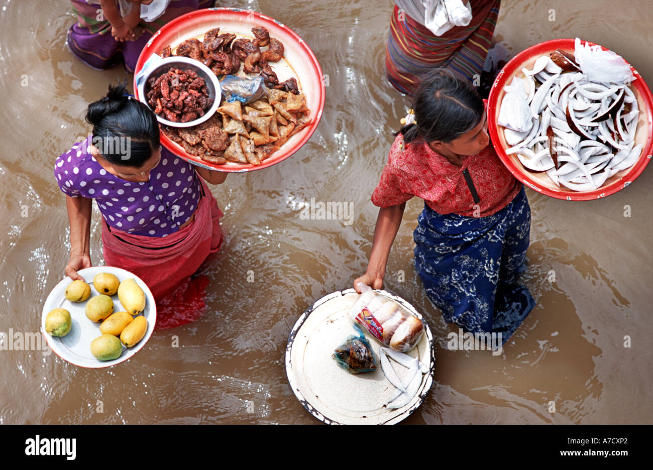 Women selling food from plates and trays to passengers on a passing boat En Route from Mandalay to Bagan Burma Myanmar - Stock Image