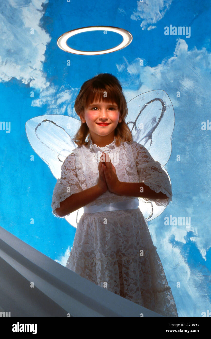 Praying child as angel in heaven with halo - Stock Image