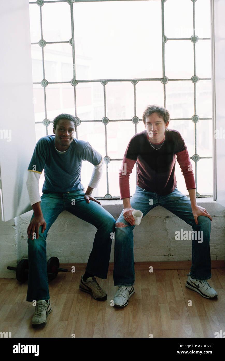 two men black white sitting on window ledge mimicking each others pose - Stock Image