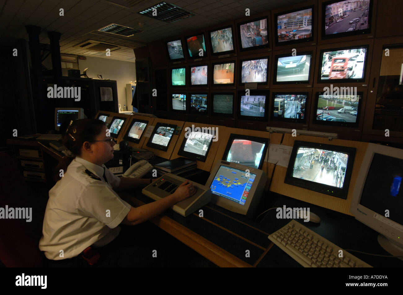 A CCTV operator at Brighton police station controls a bank of screens showing images from CCTV  cameras monitoring the streets - Stock Image