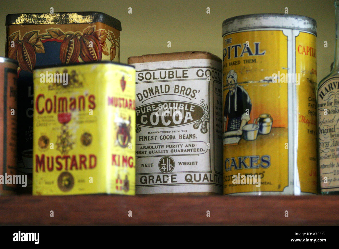 Antique tins on a parlour shelf - Stock Image