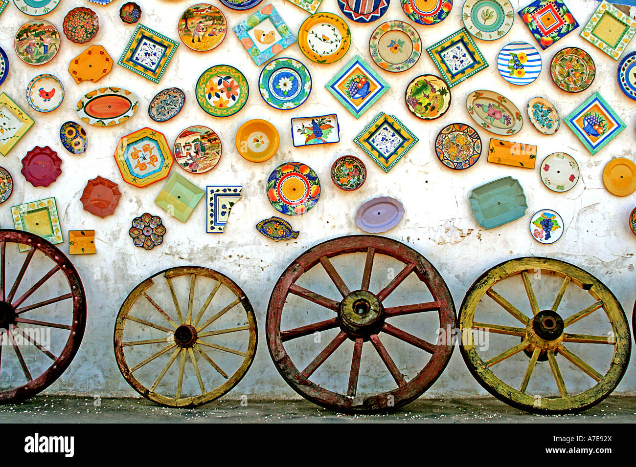 Pottery display and wagon wheels outside shop Raposeira Algarve Portugal Europe - Stock Image