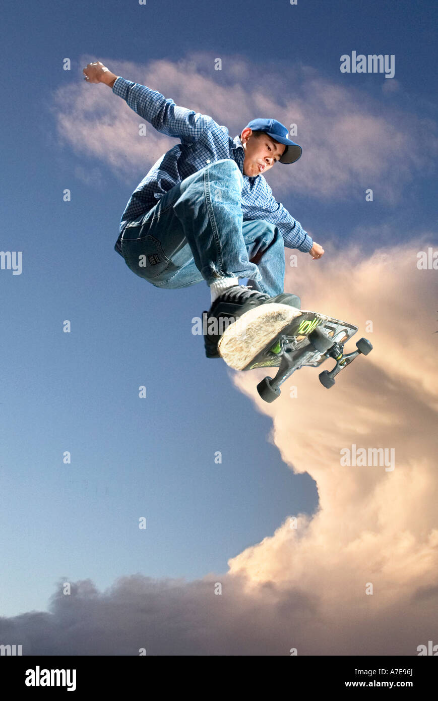 Asian American boy rides skateboard up in the sky. - Stock Image