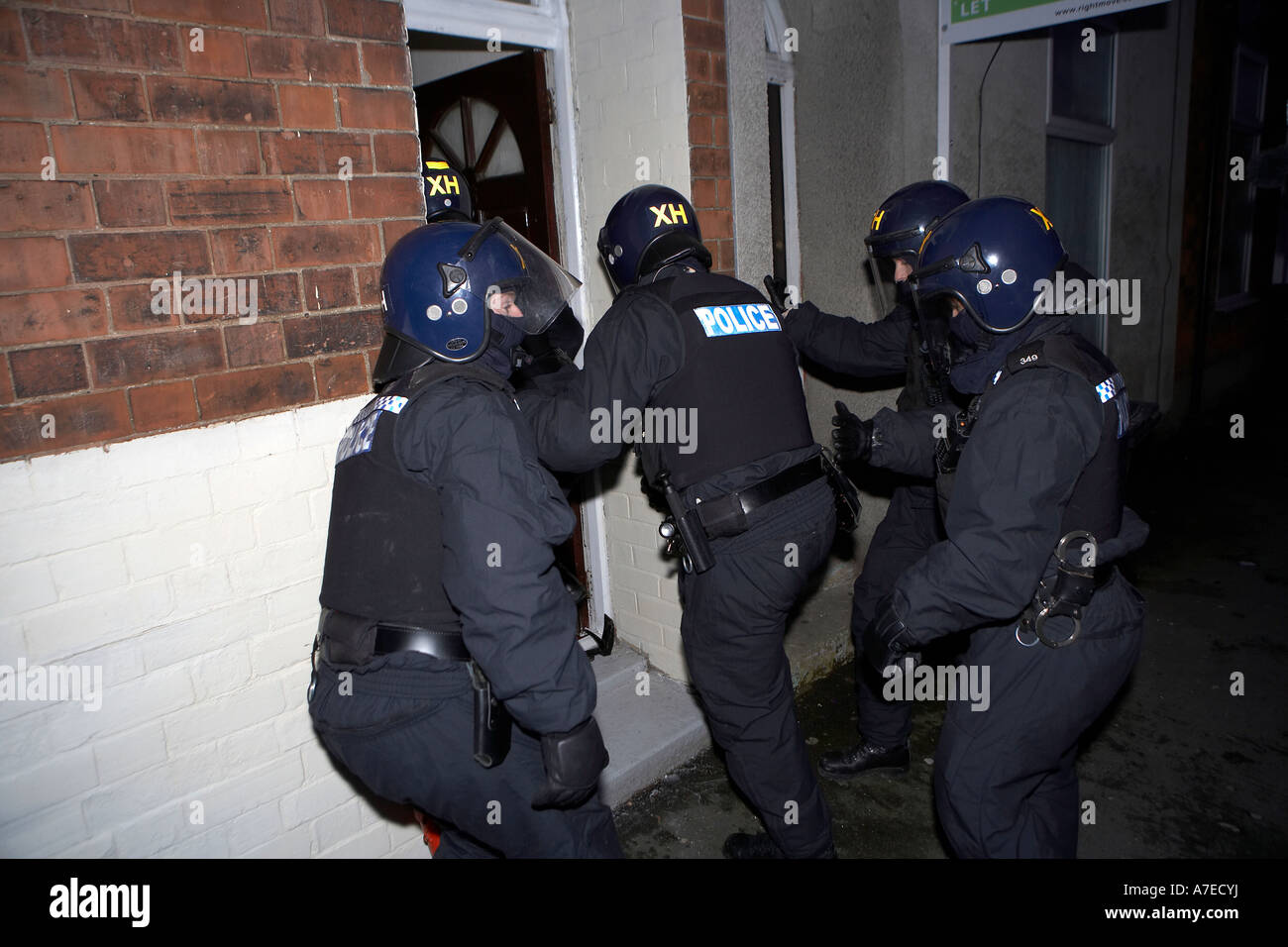 Police enter a house after breaking down a front door during a dawn raid on suspected drugs dealers in Hull East Yorkshire & Police enter a house after breaking down a front door during a dawn ...