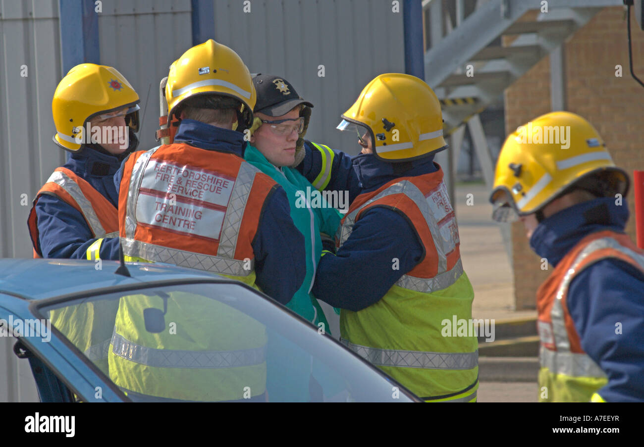 Fire recruits tackle a simulated road traffic accident as part of their passing out ceremony UK - Stock Image