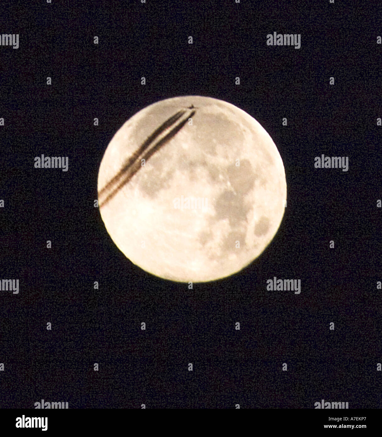 Jet airliner leaving twin vapour trails across the full moon - Stock Image