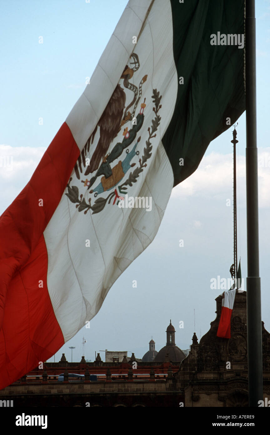 A soldier lowers the flag above the Presidential Palace, framed by Mexican flag over the Zocalo. - Stock Image
