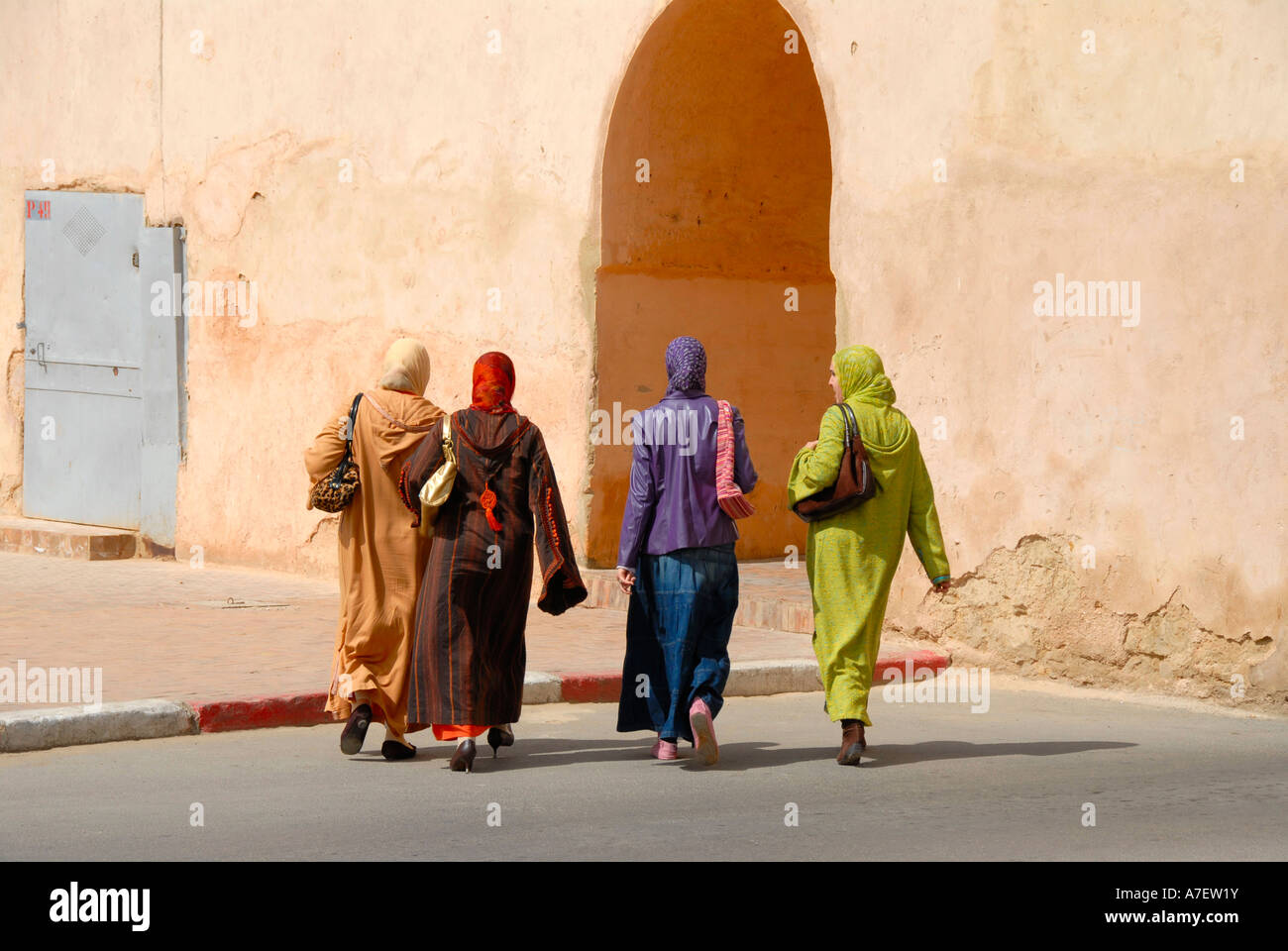 Tradition and modernity four women dressed colourfully at gate Meknes Morocco - Stock Image
