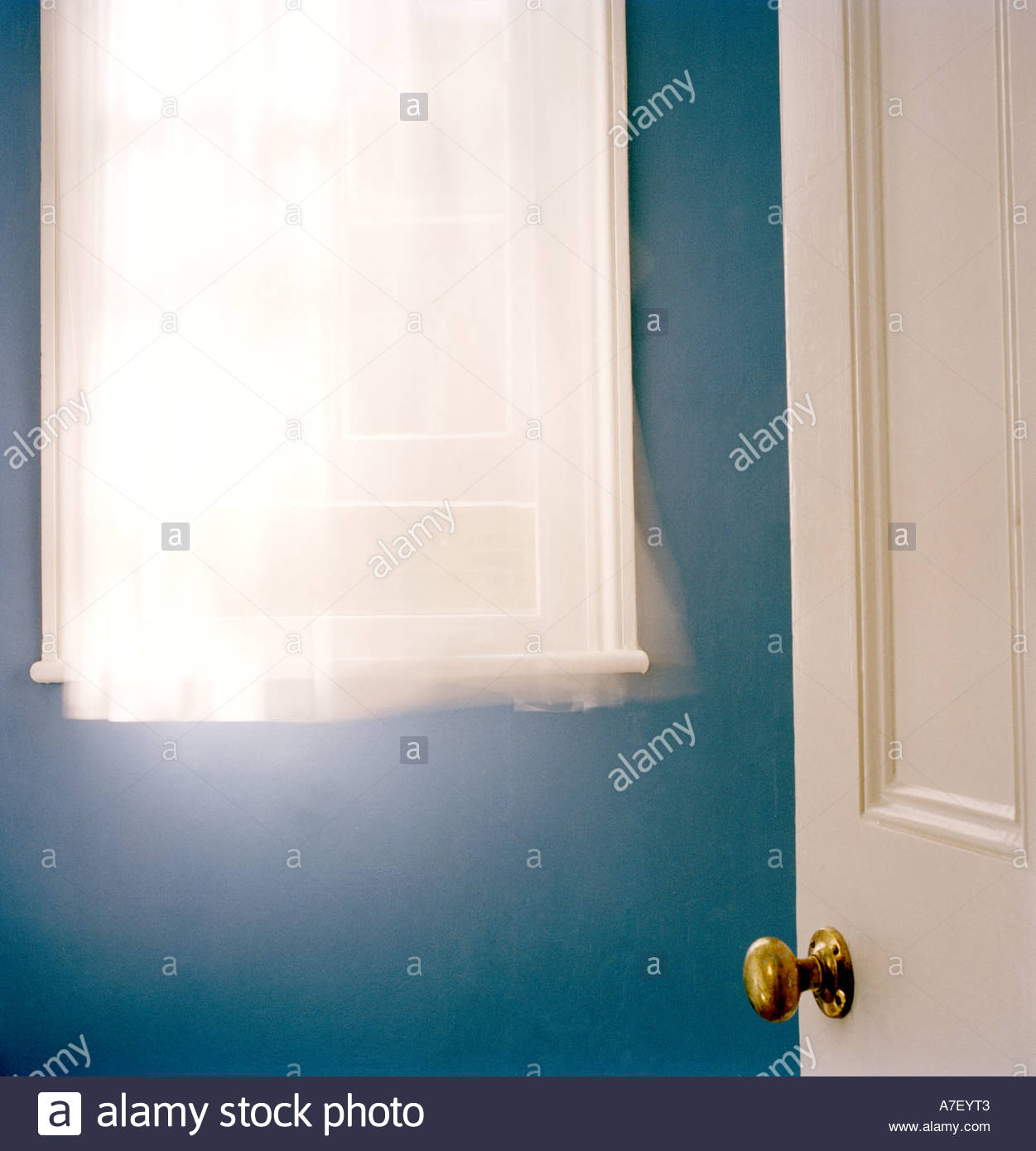 Curtain blowing in the window with open window and open door - Stock Image
