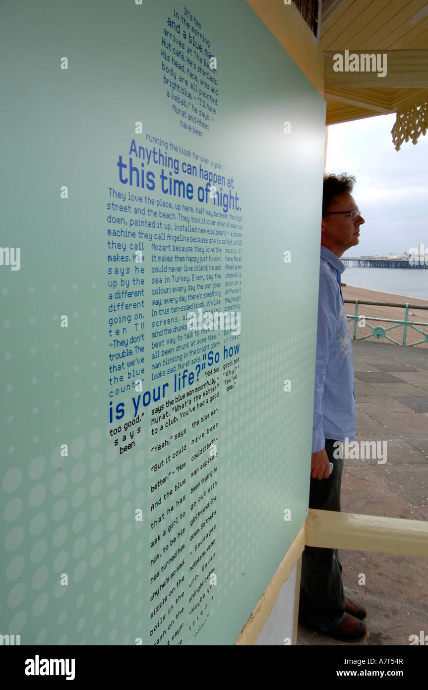 Writer William Shaw with a short story on a seafront cafe wall - Stock Image