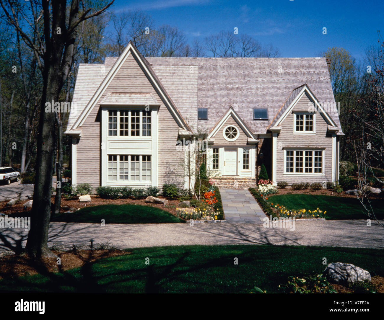 English cottage with slate walk brick steps copper drains on wood shingle roof and siding skylights framed port hole window - Stock Image