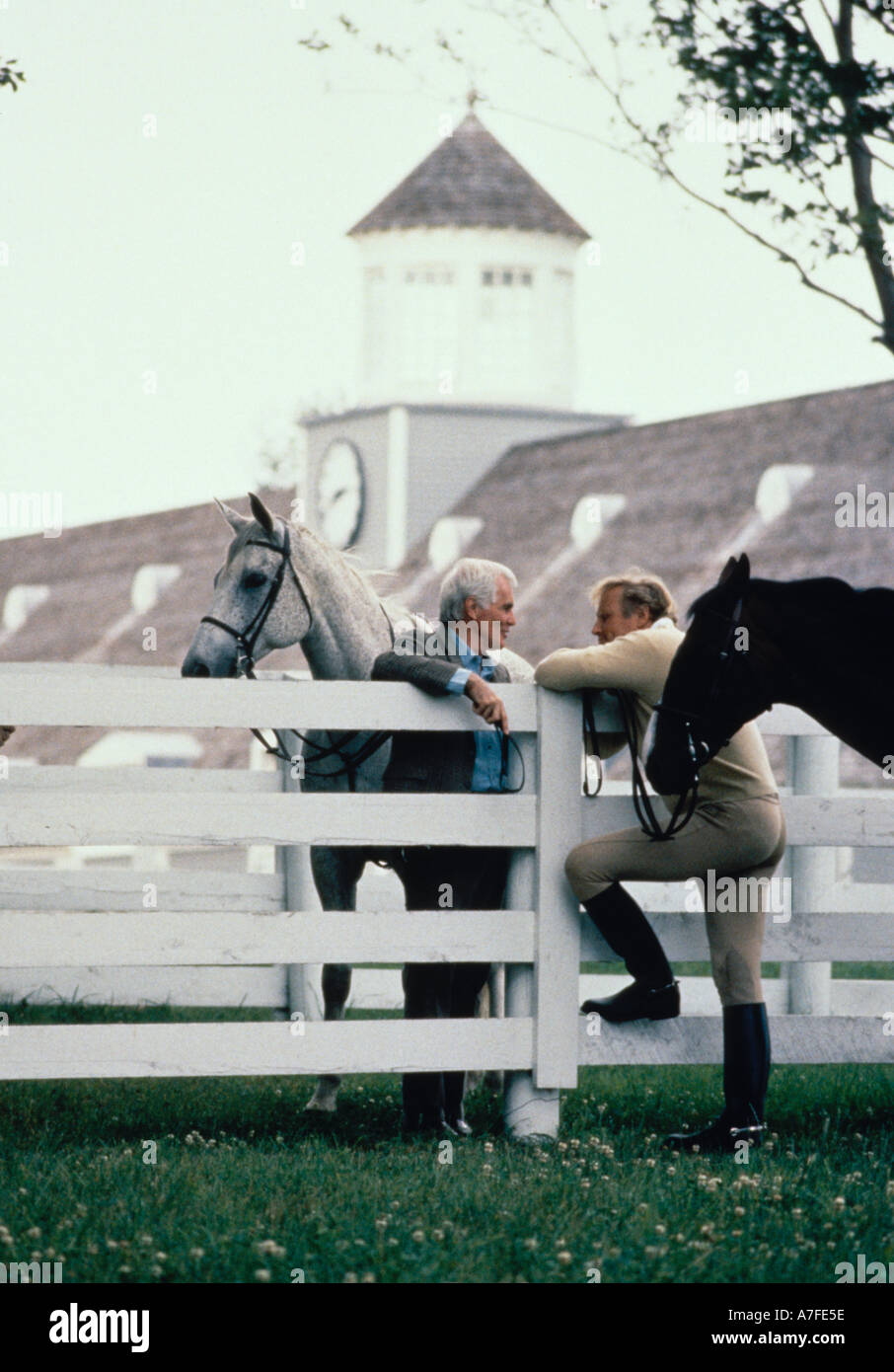 Two men with horses talking over a white fence - Stock Image
