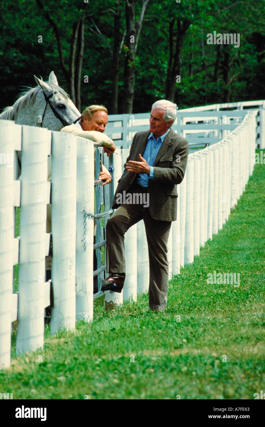 Horse buyer talking to horse trainer over white fence - Stock Image