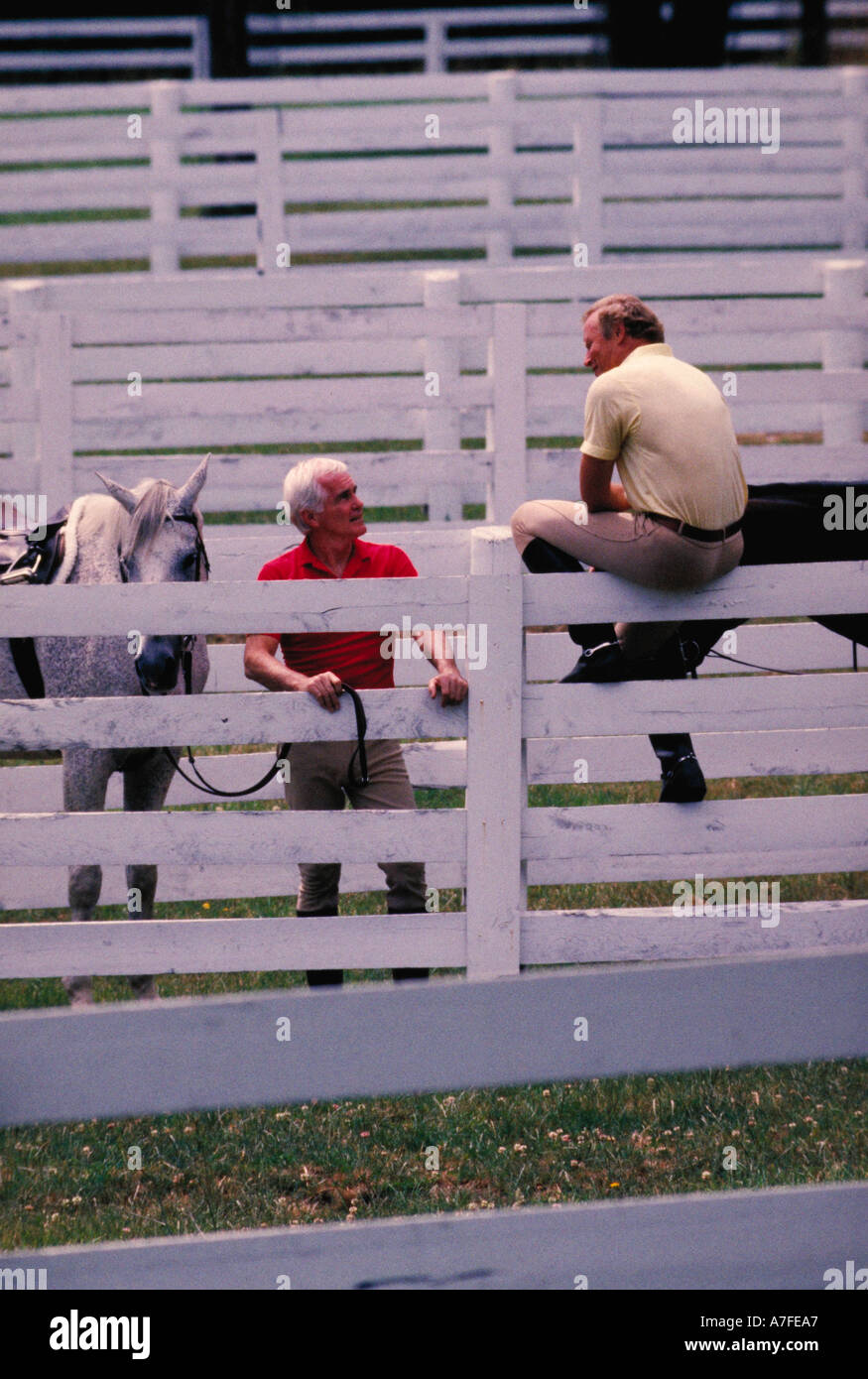 Two men with horses talking over white fence Stock Photo