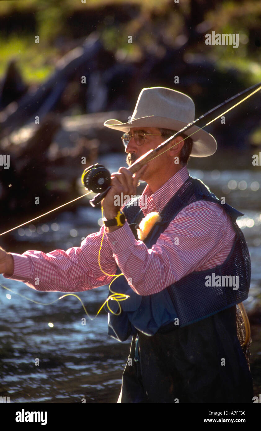 Man wearing a cowboy hat while fly fishing in a river in the Stock ... fe6b8f555b57