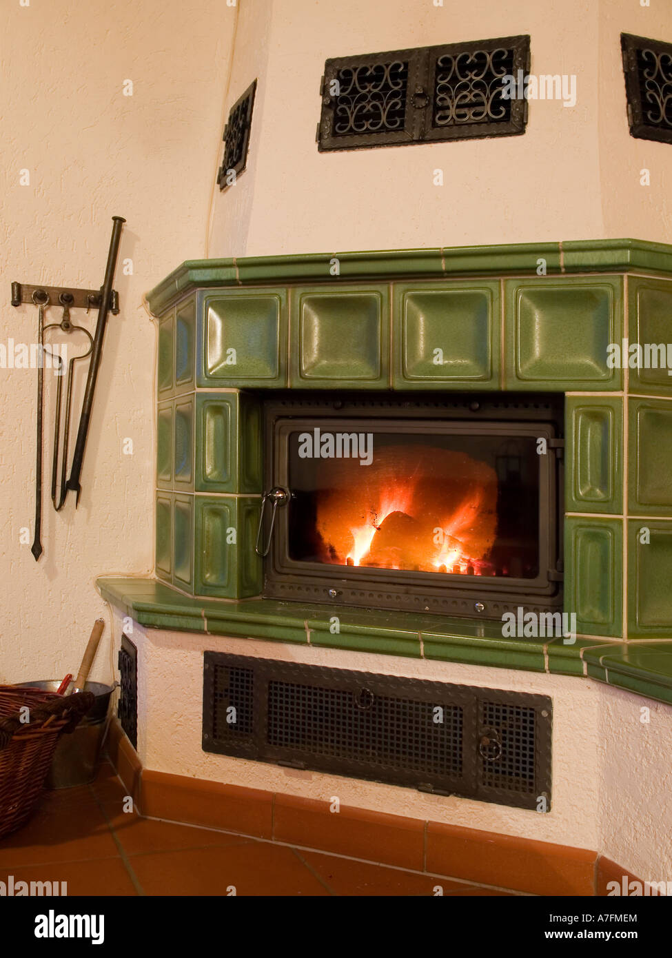 tiled stove burning with firewood in typical German way - Stock Image