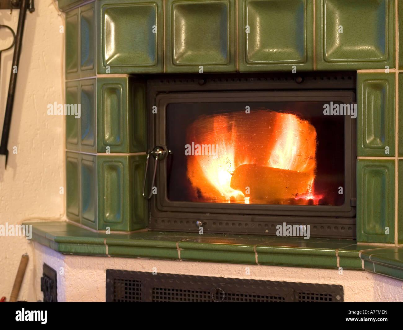 burning tiled stove burning with firewood - Stock Image