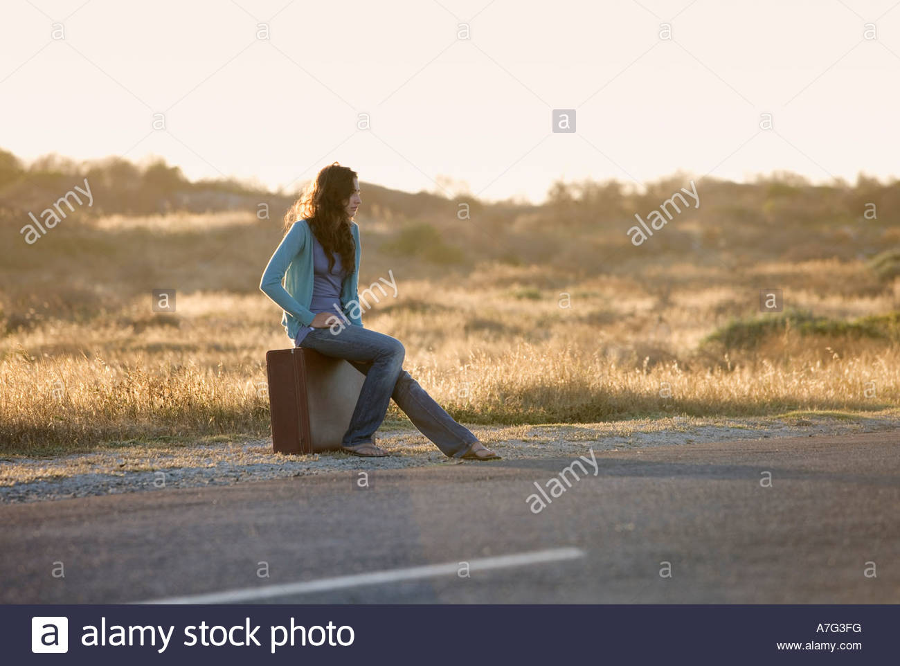 A woman with a suitcase hitching a lift - Stock Image