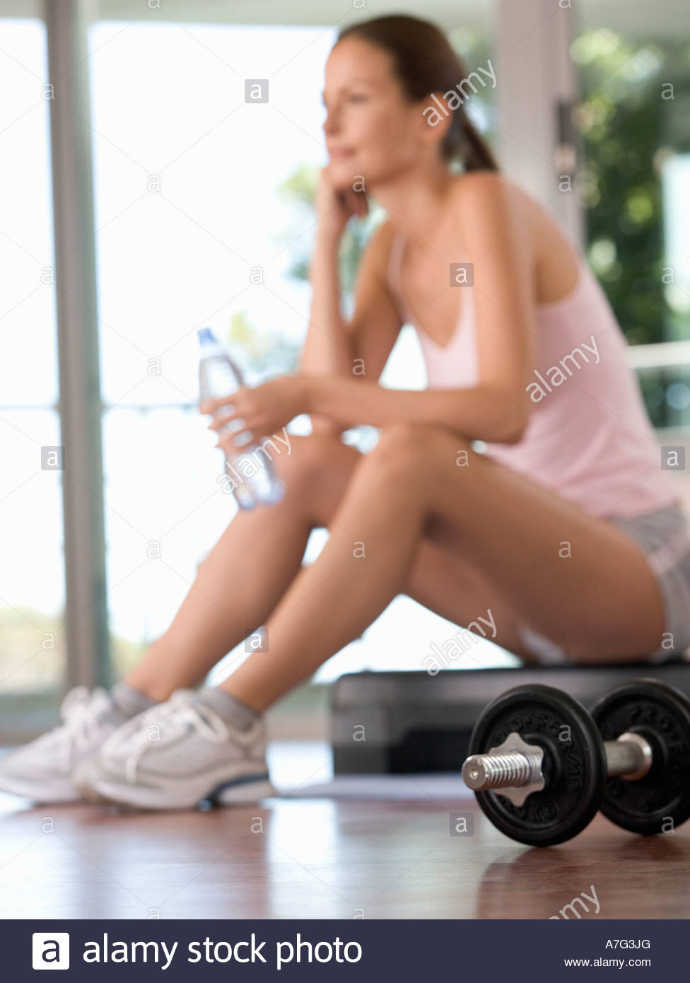 A woman sitting in a gym - Stock Image