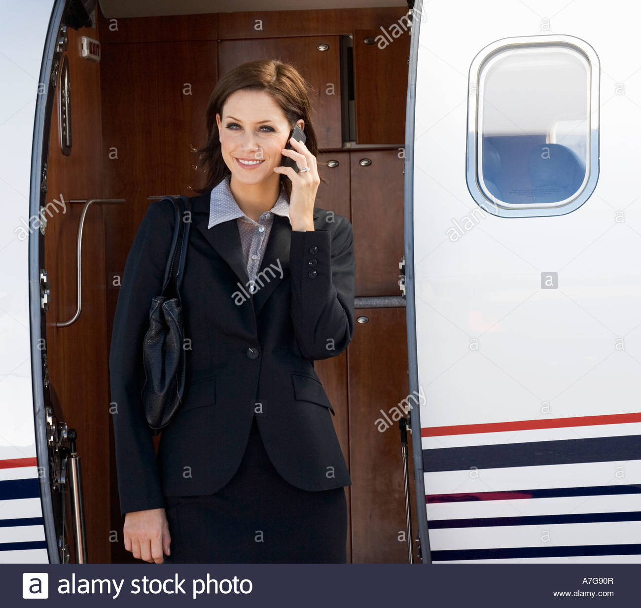 A business woman talking on a mobile phone next to a plane - Stock Image