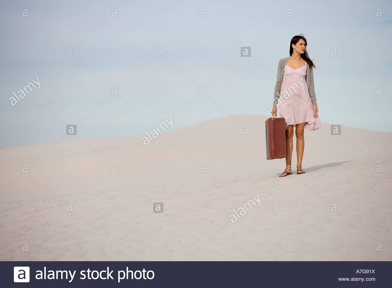 A young woman walking in the desert carrying a suitcase - Stock Image