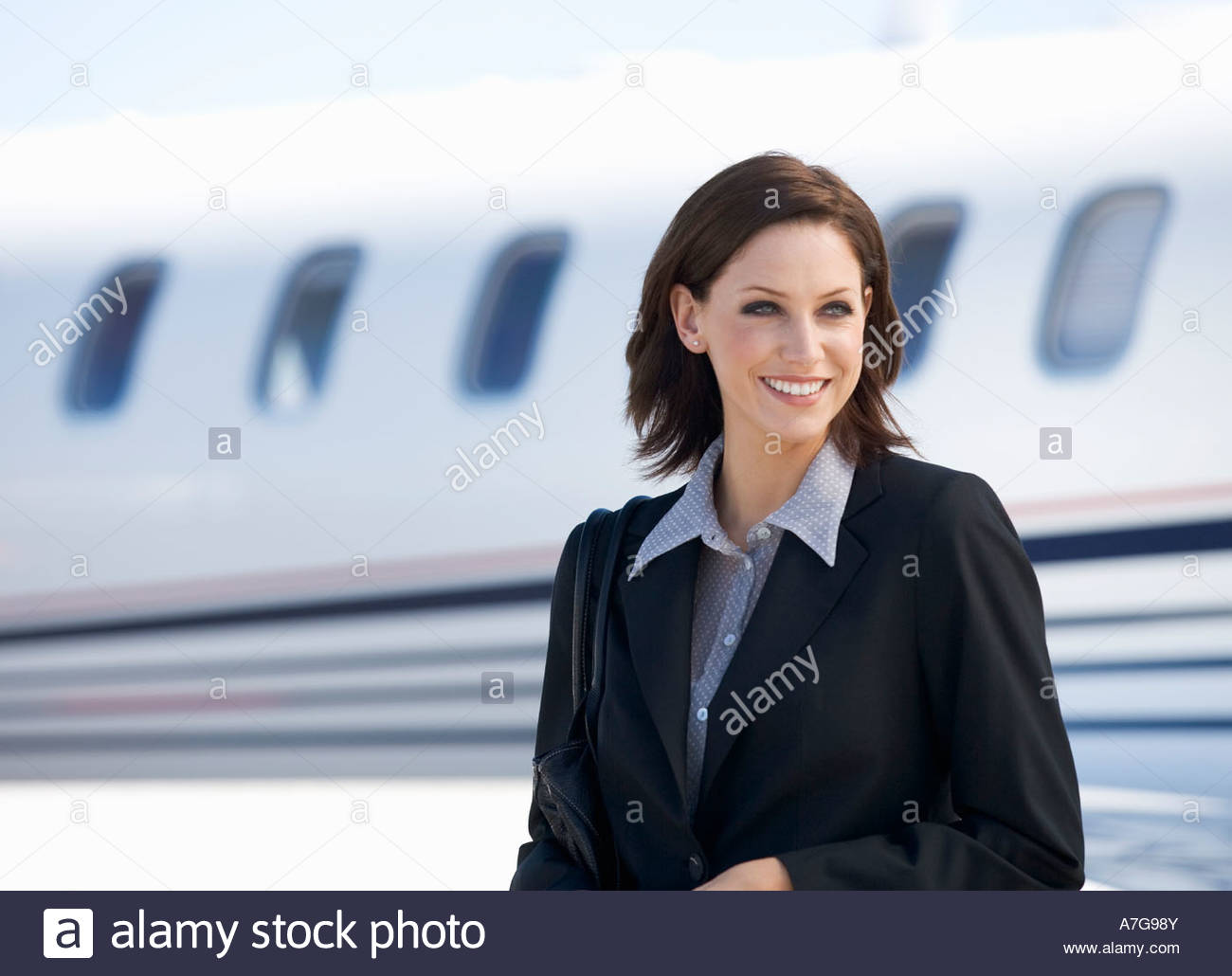 A business woman standing by a plane - Stock Image