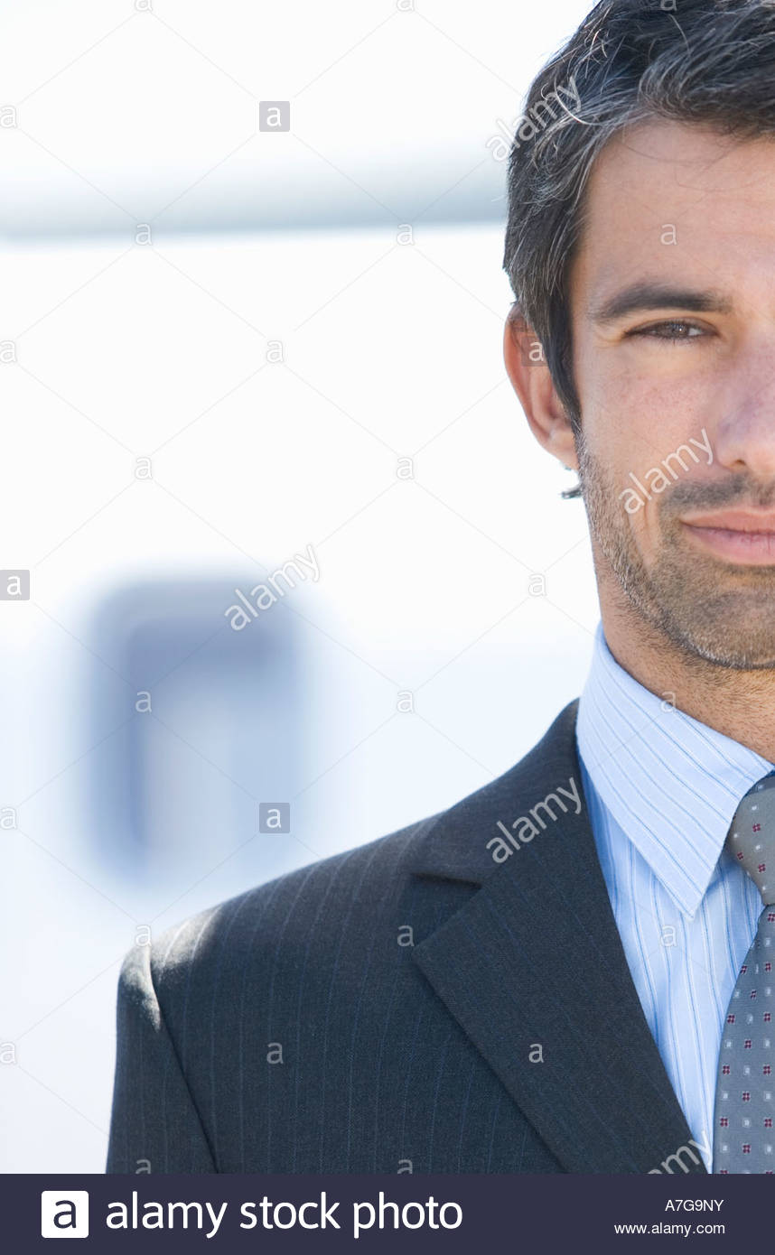 A businessman standing by a plane - Stock Image