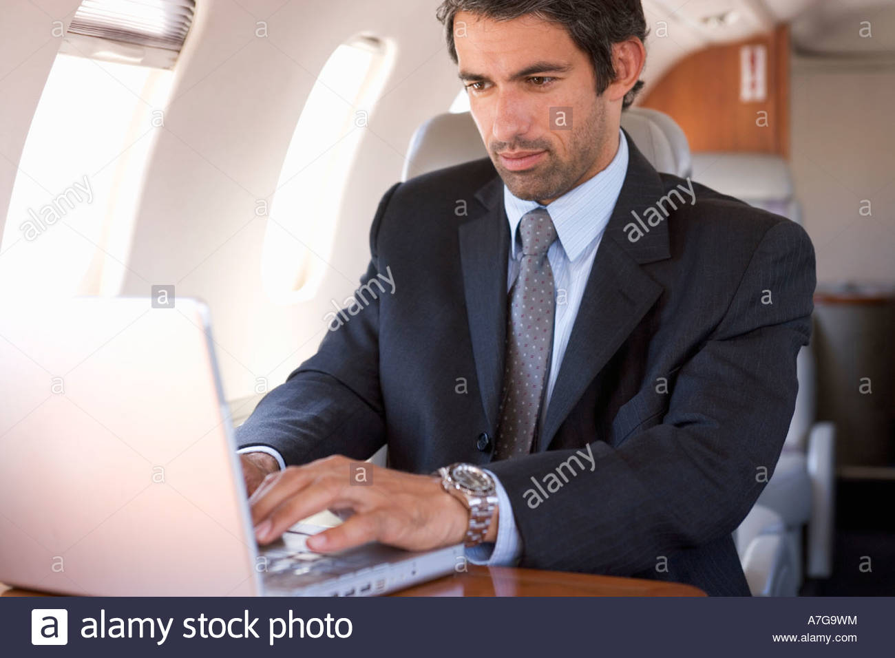 A businessman using a laptop in a plane - Stock Image