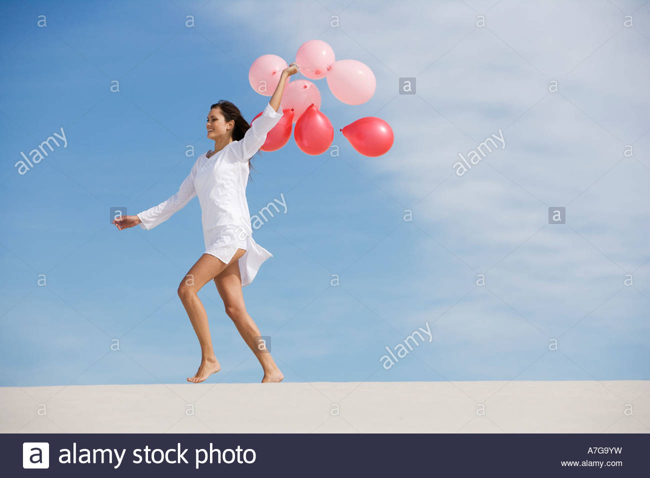 A woman walking in the desert holding a bunch of balloons Stock Photo