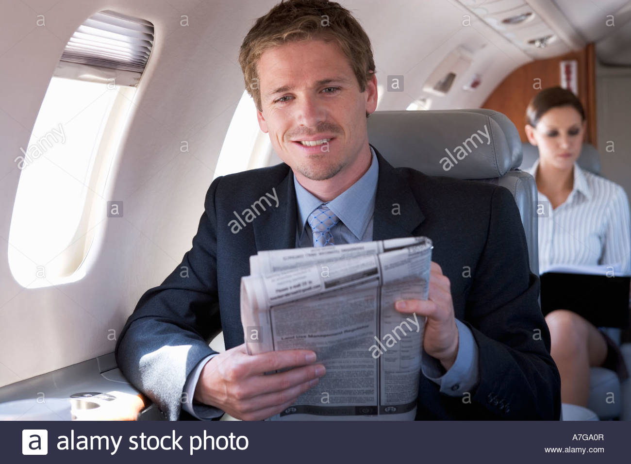 A businessman reading the paper on a plane - Stock Image