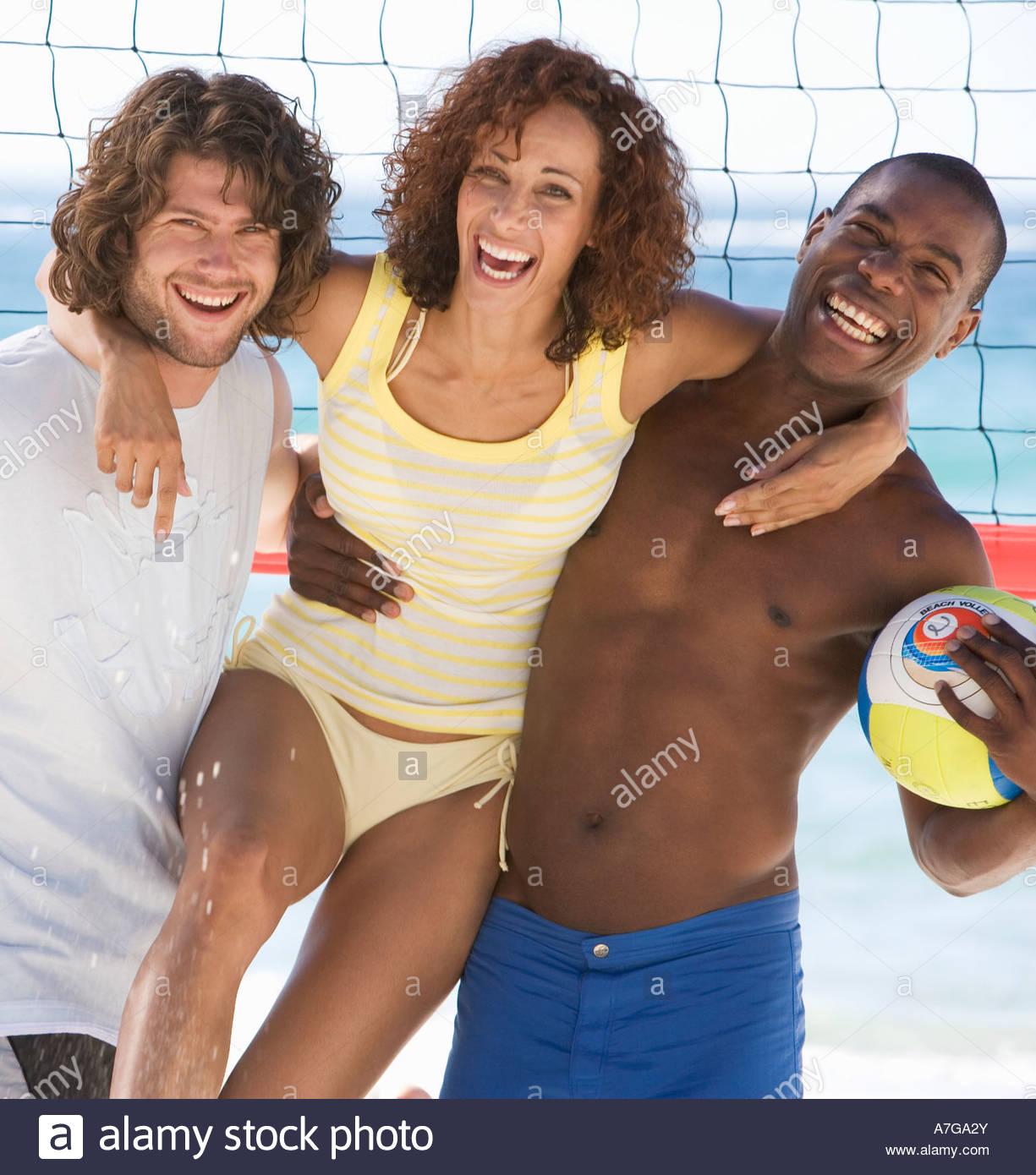 Three friends on a beach - Stock Image
