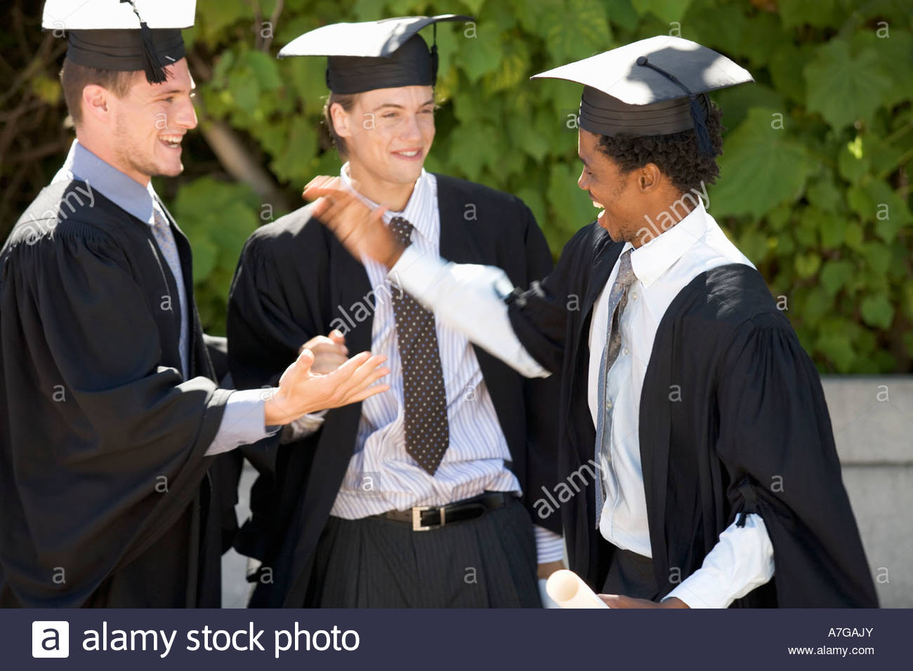 Three graduates celebrating - Stock Image