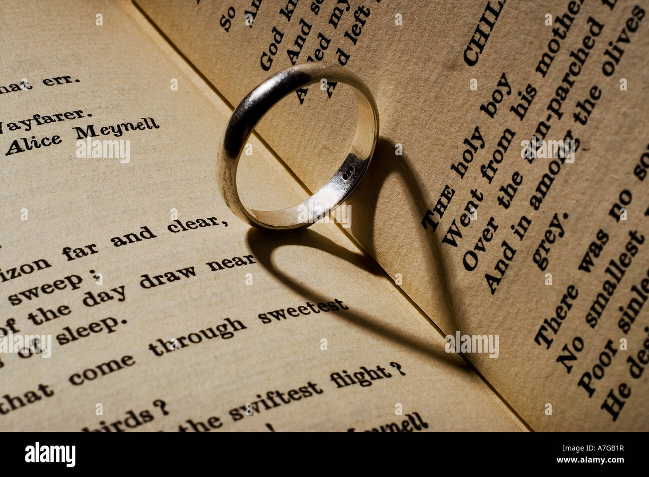 Wedding ring casting a heartshaped shadow on a book of poetry Stock