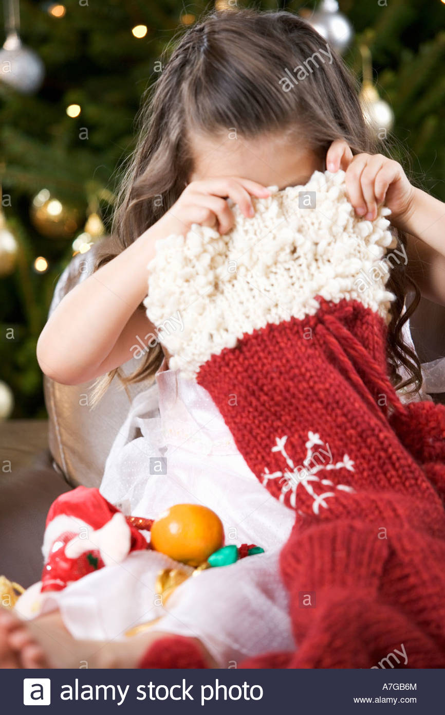 A young girl delving into a Christmas stocking - Stock Image