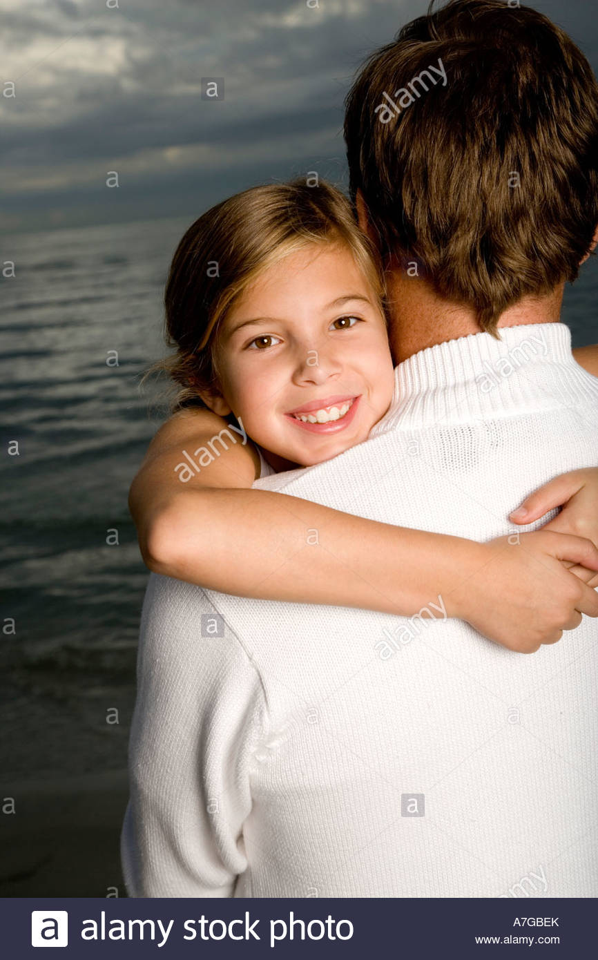 A father and daughter on a beach - Stock Image