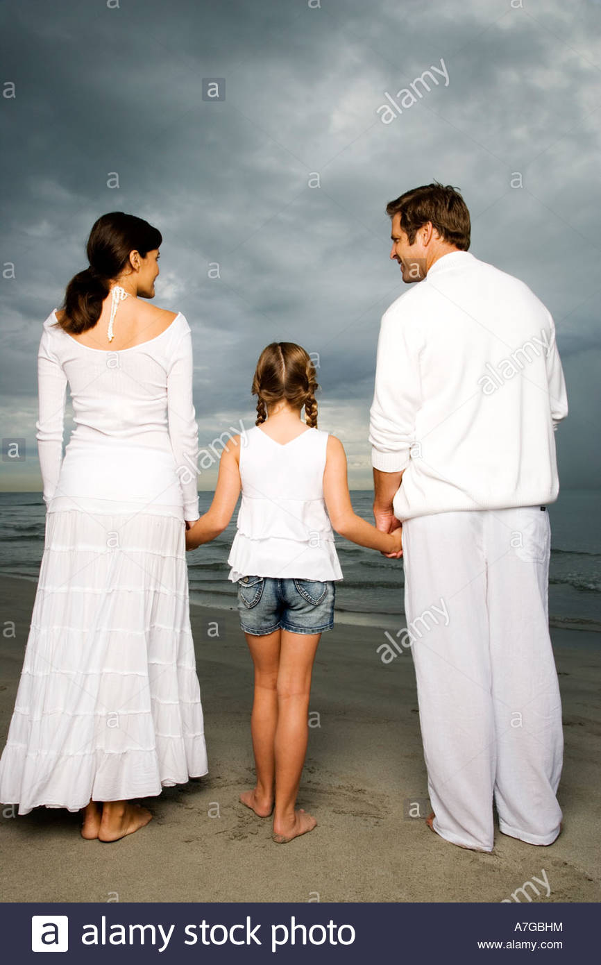 A couple with their daughter on a beach - Stock Image