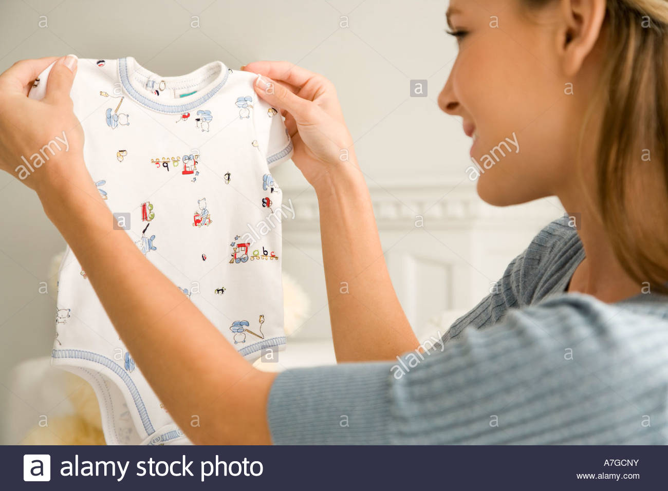 A mother holding a baby's vest - Stock Image