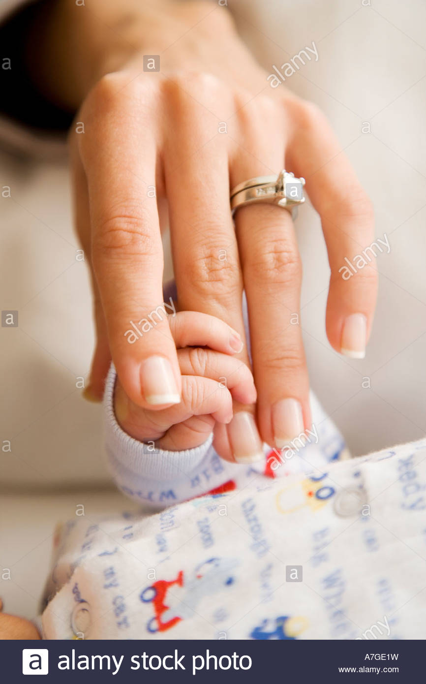A mother holding her new baby's hand - Stock Image