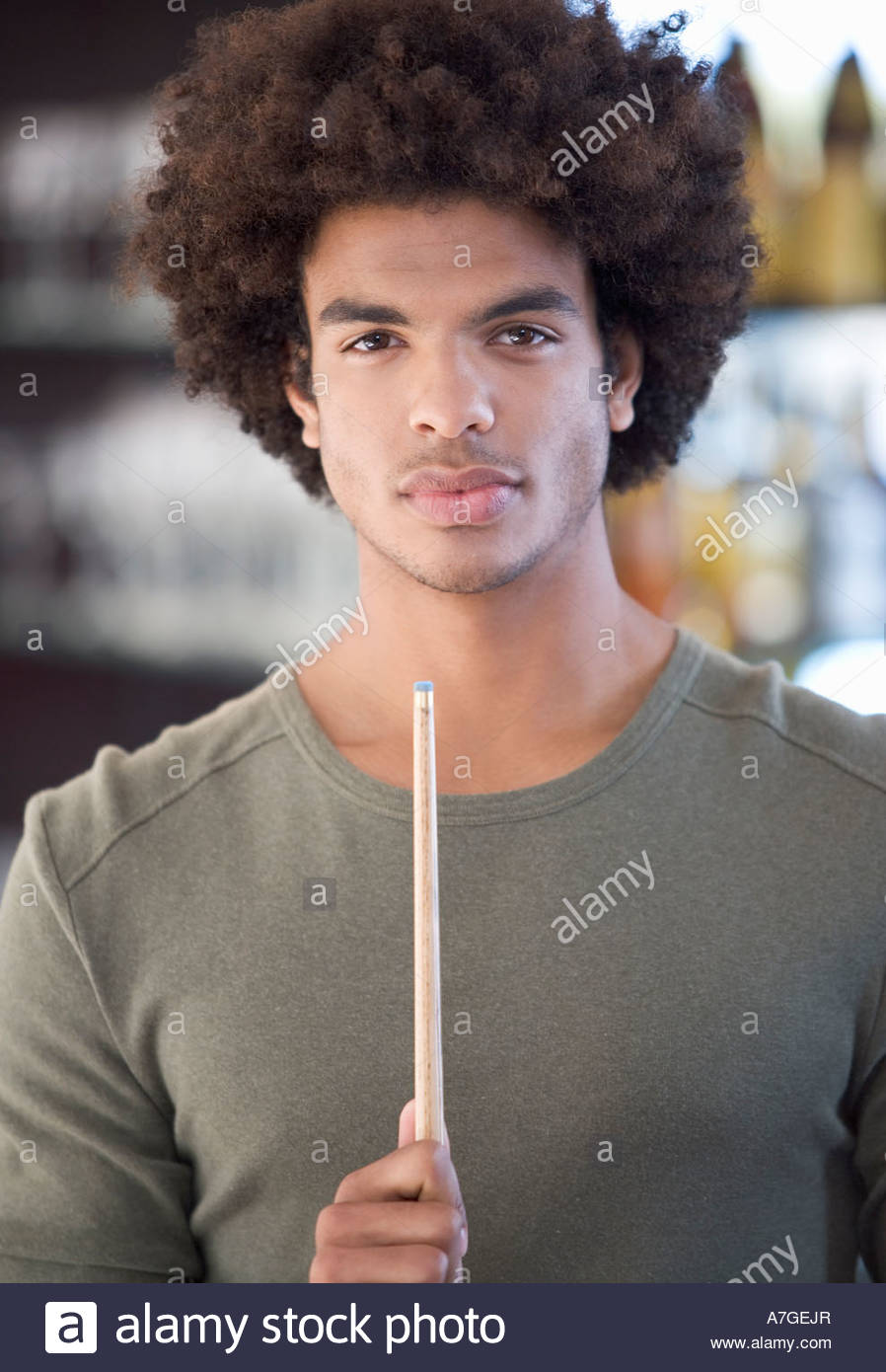 Portrait of a young man playing pool - Stock Image