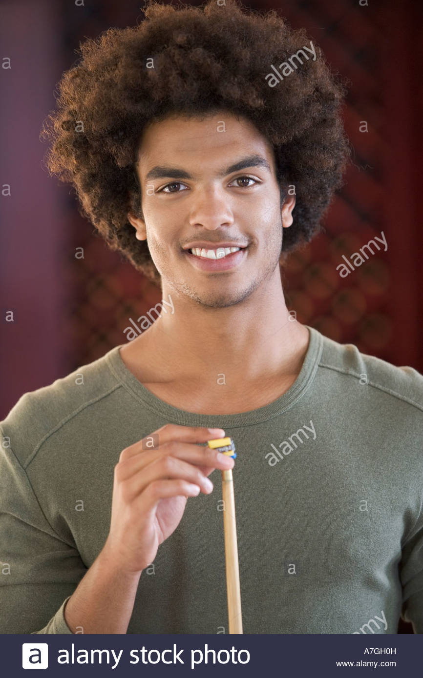 A young man playing pool - Stock Image
