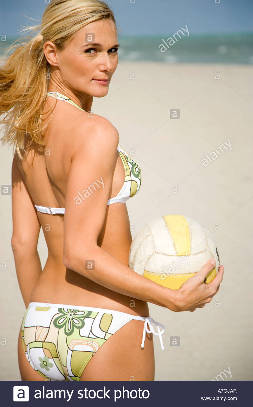 A young woman on a beach holding a ball - Stock Image