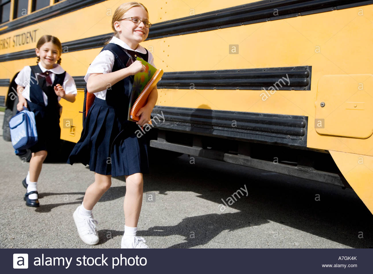 Two schoolgirls running for the school bus - Stock Image
