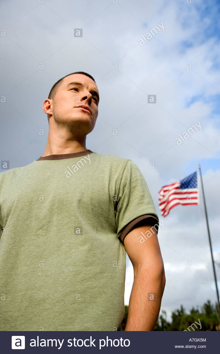 A young man standing by an American flag - Stock Image